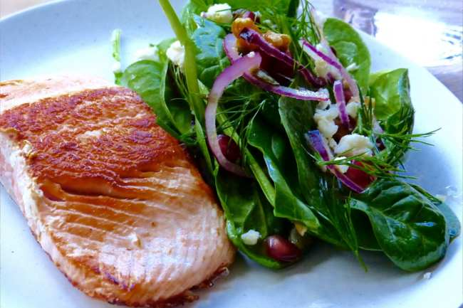 Pan-fried salmon with pomegranate, walnut and spinach salad